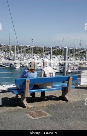 Nautical scene with elderly man and younger woman sitting together on bench seat overlooking harbour with boats - Stock Photo
