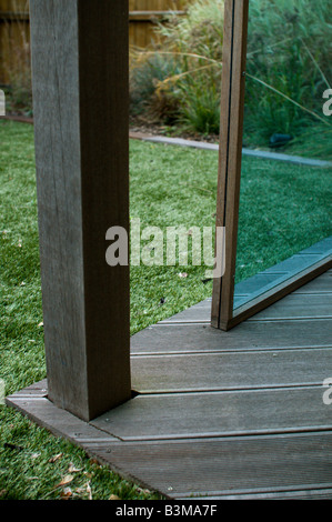 tinted perspex and wood gazebo in landscaped garden with decking and astro turf - Stock Photo