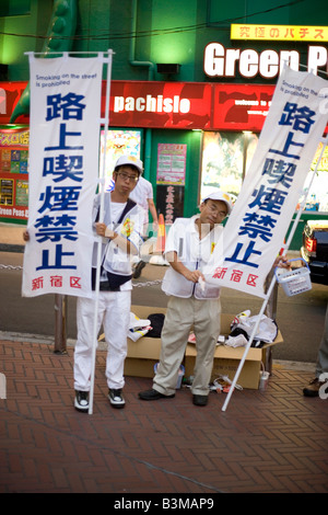 Japanese men in Tokyo hold up signs asking citizens to stop smoking cigaretttes, requesting clean air - Stock Photo