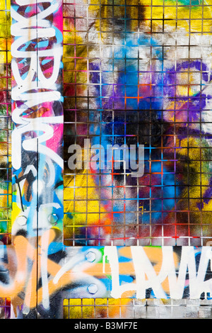 Graffiti on a chain link fence, ideal for an urban border or template - Stock Photo