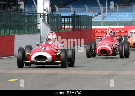 two red racing cars crossing the starting line
