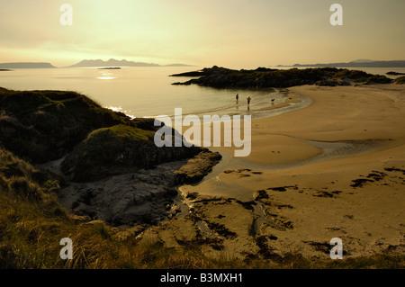 Couple walking dogs on a sandy beach at sunset, Camusdarach,Scotland - Stock Photo