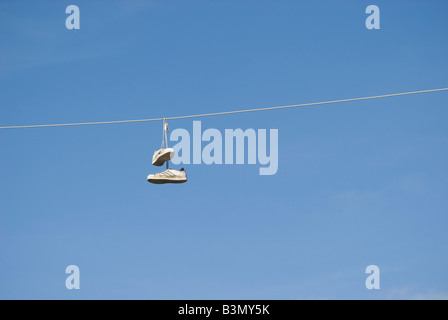 Sneakers hanging from a utility wire - Stock Photo