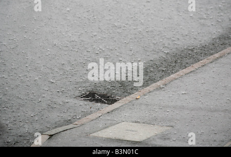 Rainwater flowing down a drain at the side of a road in Redditch Worcestershire UK during a summer storm - Stock Photo