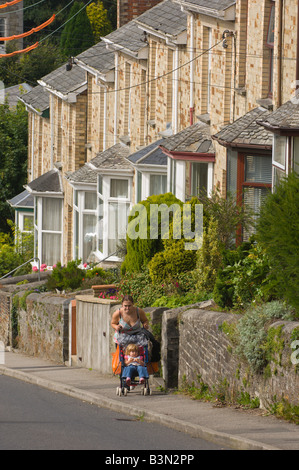 A young woman pushes a child in a pram up a steep hill in Bodmin Cornwall Great Britain Europe - Stock Photo