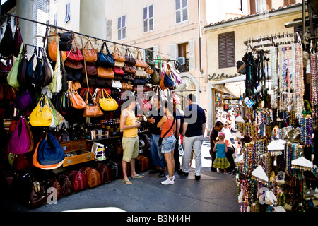 Shoppers looking at leather goods in a market in florence - Stock Photo