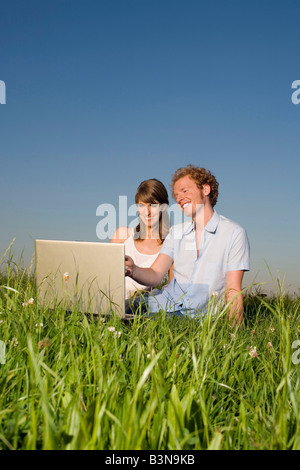 Germany, Bavaria, Young couple in meadow, using laptop, portrait - Stock Photo