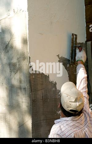 man plastering a chimney - Stock Photo