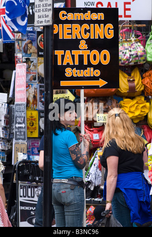 London , Camden Lock Market , pretty brunette girl in jeans , heavily tattooed arm holds sign to Camden Piercing - Stock Photo