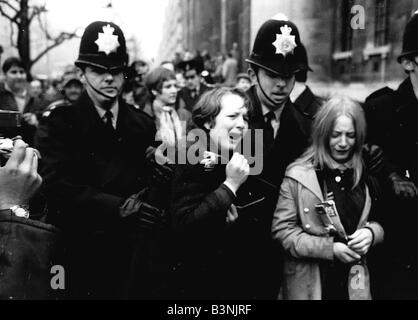 Upset Beatles fans crying because Paul McCartney got married are led away by police March 1969 - Stock Photo