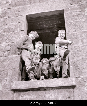 Housing slums in the Gorbals district of Glasgow where children play in the windows of derelict houses June 1966 - Stock Photo