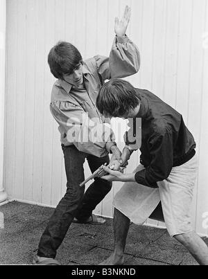Beatles Files 1964 George Harrison and Ringo Starr engage stage mock combat at the rented home in Bel Air Los Angeles - Stock Photo