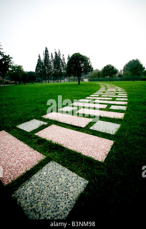 Rectangular marble tile walkway laid out on lush green grass going off into the distance - Stock Photo
