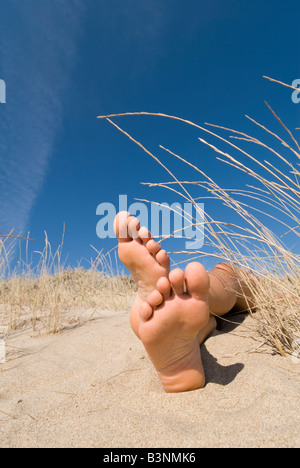 Model Released female feet lying in sand dunes with blue sky - Stock Photo