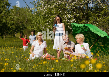 Germany, Baden Württemberg, Tübingen, Three generation family having picnic in meadow - Stock Photo
