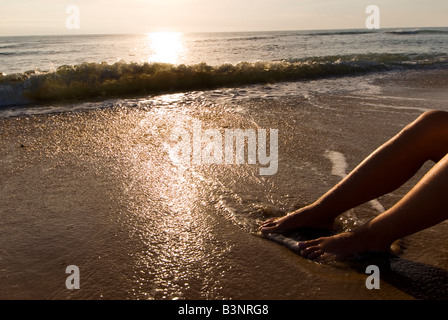 Model Released female feet being washed by the tide on a sandy shoreline - Stock Photo