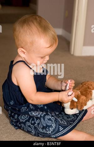 nine month old girl feels the ears of her stuffed animal dog - Stock Photo