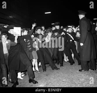 Pop Group The Beatles November 1963 Police hold back fans and crowds waiting to catch a glimpse of their idols in - Stock Photo
