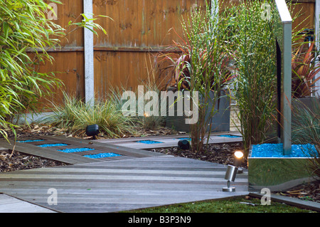 modern landscaped garden with water feature and astro-turf lawn and decking - Stock Photo