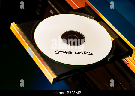Pirated DVD disk movie sitting in the DVD tray about to be played - Stock Photo