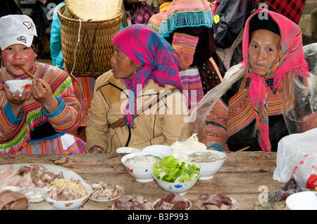 A Flower Hmong woman and her family sit at a food stall Vietnam - Stock Photo
