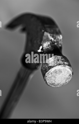 Black and white image of the head of a well used hammer poised to drop - Stock Photo