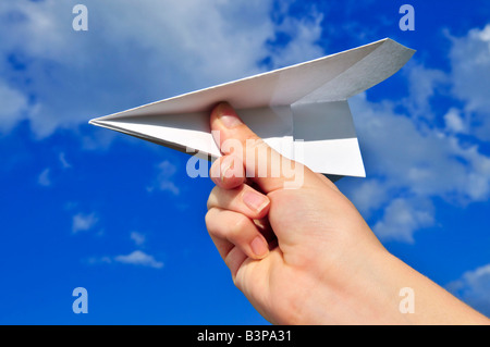 Child s hand holding a paper airplane on blue sky background - Stock Photo