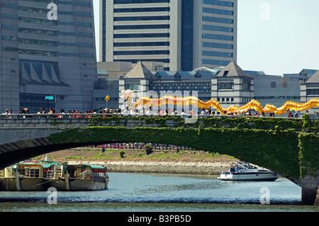 Japan, Kanagawa prefecture, Yokohama. Chinese Dragon dancers crossing the city bridge during the International parade. - Stock Photo