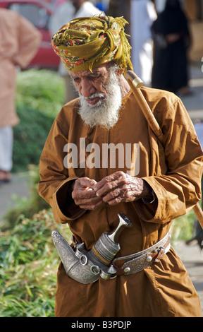 Old man wearing Khanjar or Omani dagger Sinaw Sharqiya Region Sultanate of Oman - Stock Photo