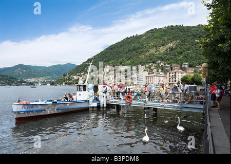 Tourists boarding a ferry on the lakefront at Como, Lake Como, Lombardy, Italy - Stock Photo