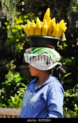 Girl carrying cooked ears of corn on her head near Lake Bratan, Bali, Indonesia - Stock Photo