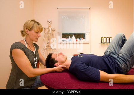 Physiotherapist, teacher of the Alexander technique guiding a patient through a relaxation exercise for the throat - Stock Photo