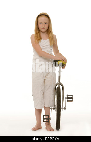 8-year-old red-haired girl standing next to her unicycle - Stock Photo