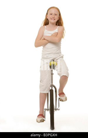 8-year-old red-haired girl sitting on her unicycle - Stock Photo