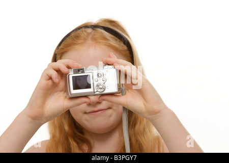 8-year-old red-haired girl taking pictures of herself with a digital camera - Stock Photo