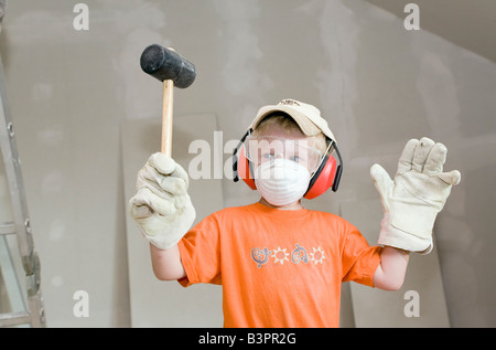 A boy, aged four, playing with work gloves, safety goggles, respiratory and hearing protection as well as a hammer - Stock Photo