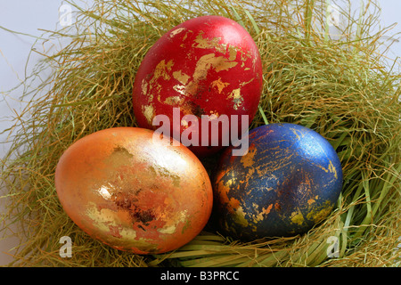 Coloured easter eggs with golden ornament in an easter basket - Stock Photo