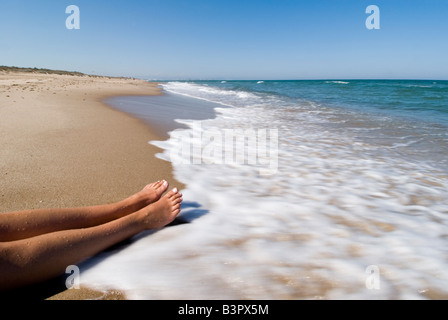 Model Released woman with outstretched legs letting waves wash over her body - Stock Photo