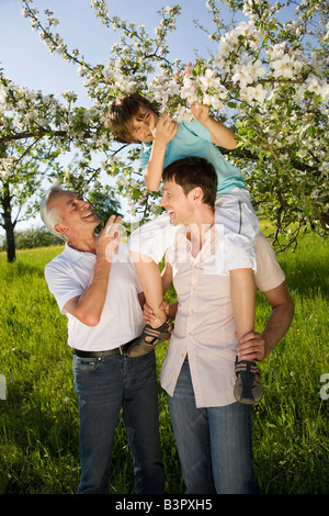 Germany, Baden Wrttemberg, Tbingen, Three generation family,  Boy (11) sitting on father's shoulders, looking at - Stock Photo