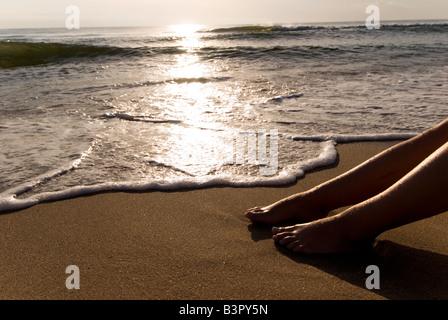 Model Released female feet beside sea on a sandy shoreline - Stock Photo