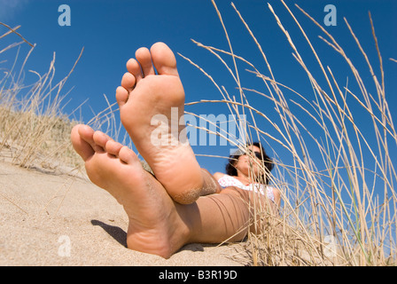 Model Released female feet lying in sand dunes with blue sky and focus on feet - Stock Photo