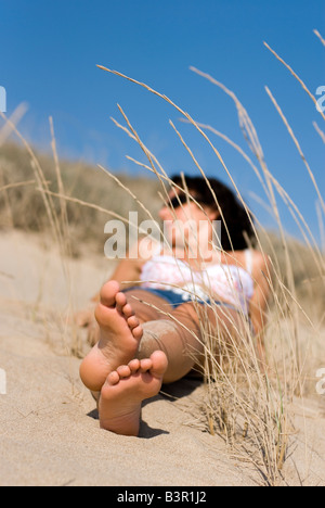 Model Released female lying in sand dunes with blue sky and focus on feet - Stock Photo