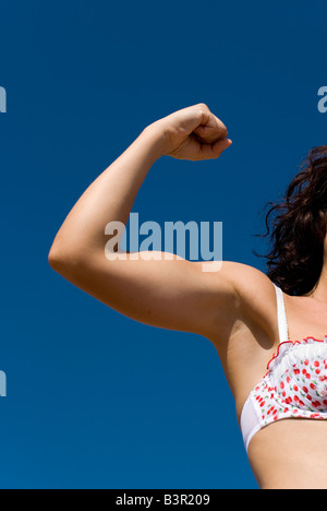 Model Released female arm flexing biceps against a clear blue sky wearing feminine floral bra - Stock Photo