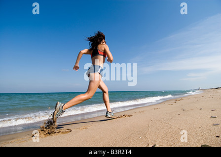 Model Released fit young woman running along shoreline of an empty sandy beach - Stock Photo