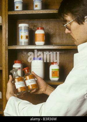 lab technician holds reagent bottles of corrosive chemicals - Stock Photo