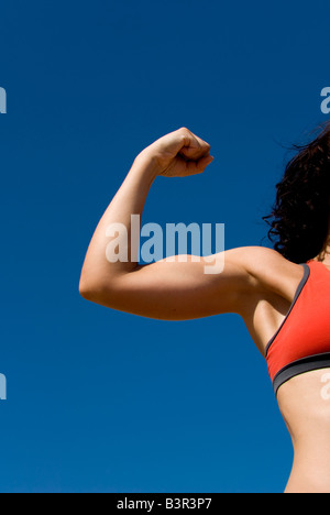 Model Released sporty female arm flexing biceps against a clear blue sky - Stock Photo
