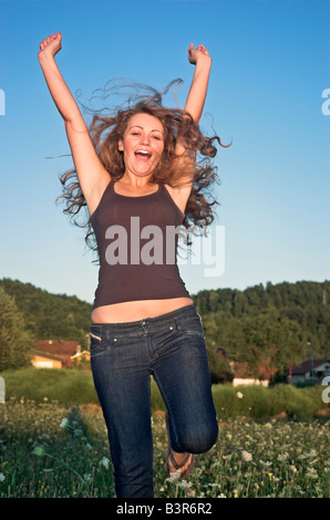Cheerful teenage girl 16 18 jumping in field with arms raised - Stock Photo