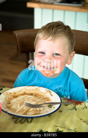 Young happy boy with food on his face and empty plate in front of him grinning at the dinner table - Stock Photo