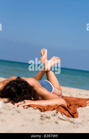 Model Released female sunbather laying on sandy beach with focus on feet - Stock Photo