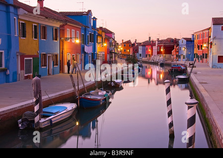 Burano Venice Italy canal reflections at dusk with boats and colorful fishermen houses reflecting on water at clear - Stock Photo